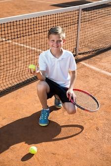 Garoto agachado segurando a bola de tênis