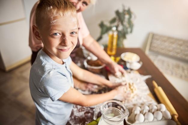 Garoto alegre aproveitando o tempo na cozinha com sua avó gentil