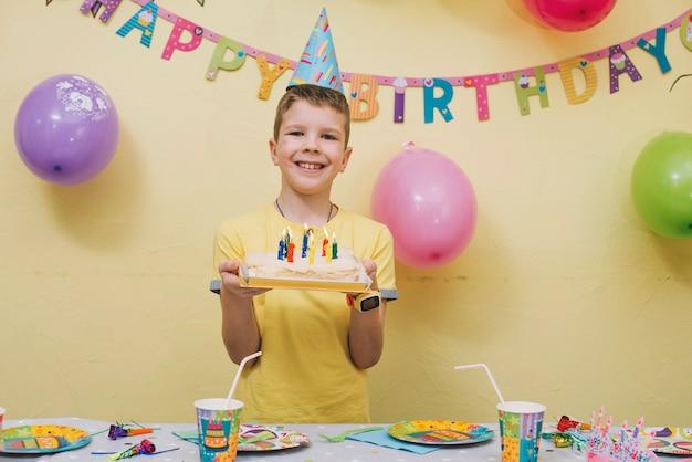 Garoto alegre com bolo de aniversário