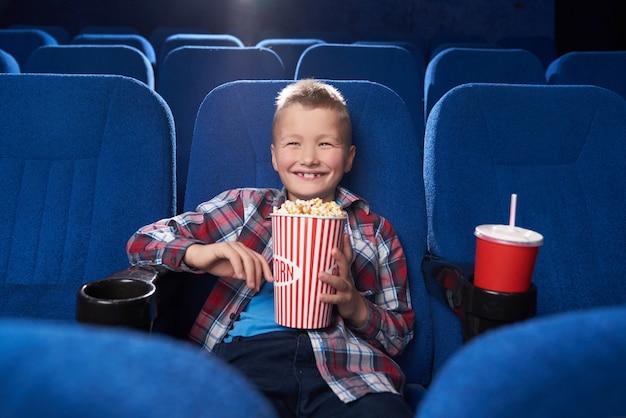 Garoto alegre rindo, assistindo filme de comédia no cinema.