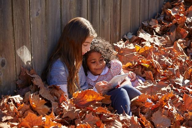 Garoto amigas jogando tablet pc em folhas de outono