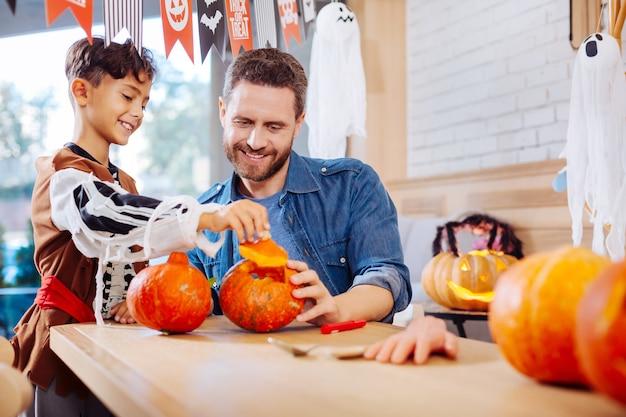 Garoto animado. menino de cabelos escuros usando fantasia de halloween se sentindo animado antes da festa perto do pai