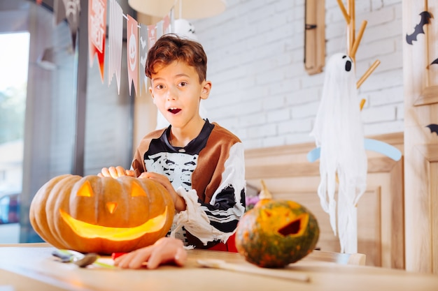 Garoto animado. menino fofo e engraçado usando fantasia de esqueleto de sentimento animado ao ficar perto da abóbora esculpida de halloween