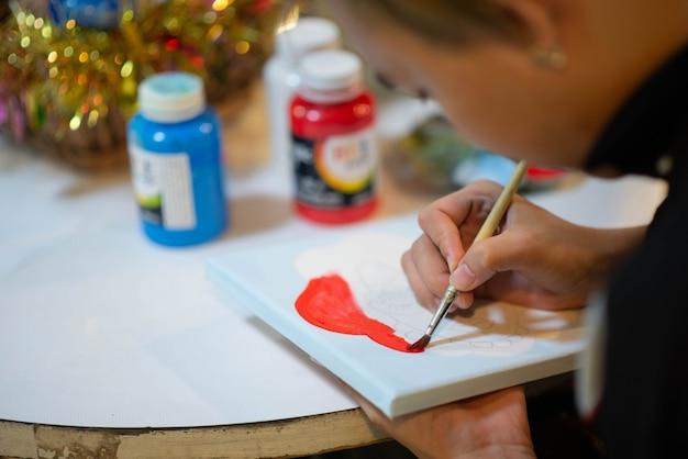 Garoto aprendendo pintura de arte e artesanato na sala de aula de arte