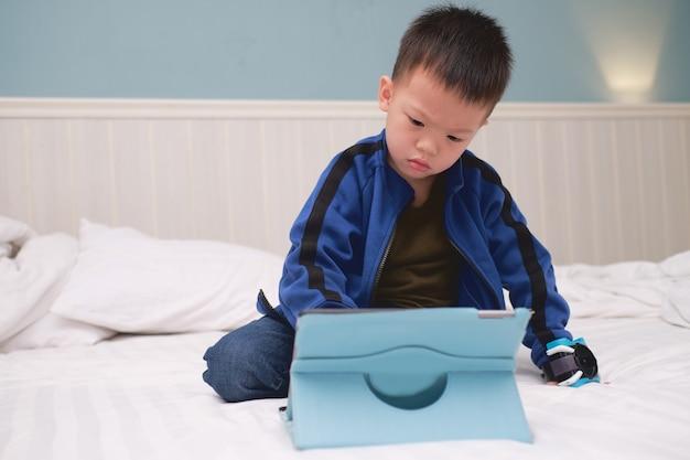 Garoto asiático agressivo confuso de 3 a 4 anos de idade sentado na cama assistindo a um vídeo, jogando no tablet pc, crianças brincando com um computador tablet, conceito de crianças viciadas em gadgets