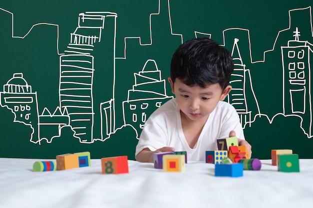 Garoto asiático brincando com arquitetura de edifício e engenheiro