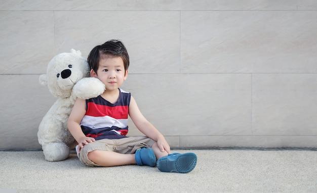 Garoto asiático com urso boneca sente-se no caminho na parede de pedra de mármore