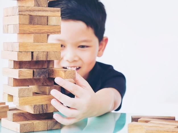 Garoto asiático está jogando jogo de torre de blocos de madeira para praticar a habilidade física e mental