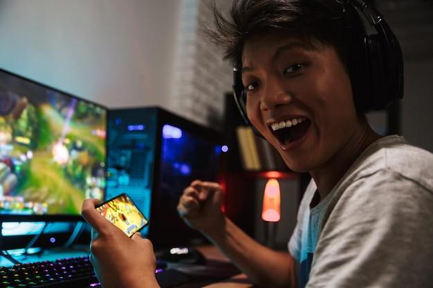 Garoto asiático feliz do jogo regozijando-se ao jogar videogame no smartphone e no computador no quarto escuro, usando fones de ouvido e um teclado colorido com luz de fundo