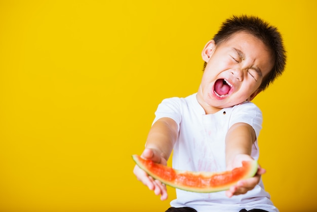 Garoto asiático lindo garotinho atraente sorriso brincando segurando um corte de melancia fresca