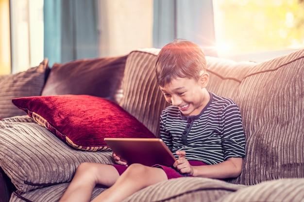 Garoto asiático segurando e jogando em seu tablet, sentado no sofá com travesseiro, sorrindo alegremente desfrutando de tempo livre, dia do sol com luz brilhando na sala de estar, vestindo camisa curta e listrada