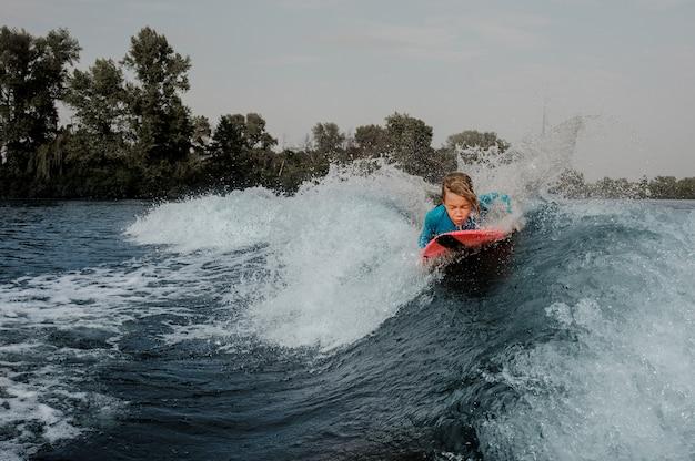 Garoto ativo deitado no wakeboard e nadar no rio