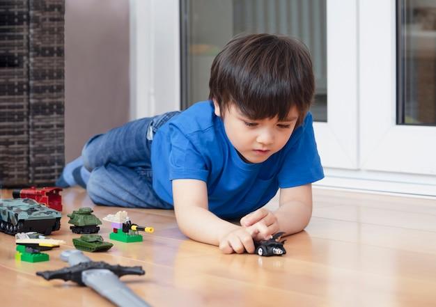 Garoto ativo, rastejando no chão, brincando com soldados e brinquedos de tanque na sala de jogos, criança feliz jogando guerras e paz por conta própria, criança relaxando em casa no fim de semana, imaginação e desenvolvimento de crianças