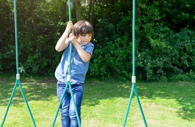 Garoto ativo, segurando o roupão no playground