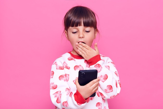 Garoto atônito feminino vestindo jumper casual, olhando para o telefone inteligente com olhar surpreso, cobrindo a boca com a palma da mão lendo notícias chocantes, posando isolado sobre a parede rosa.