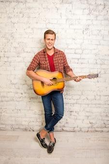 Garoto atraente em pé perto da parede tocando violão