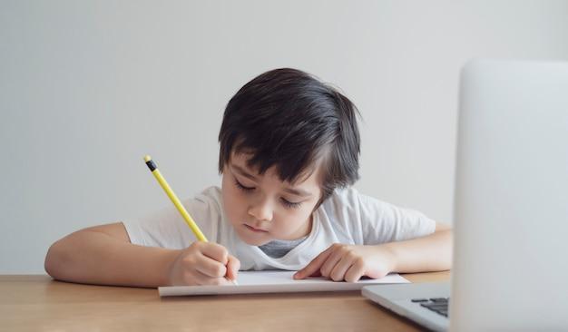 Garoto auto-isolamento usando o computador para a lição de casa, criança usando laptop pesquisando informações na internet enquanto a escola fora