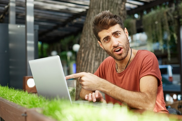 Garoto barbudo bonito confuso e surpreso fazendo perguntas sobre algo na tela do laptop, apontando para a tela com rosto maravilhado