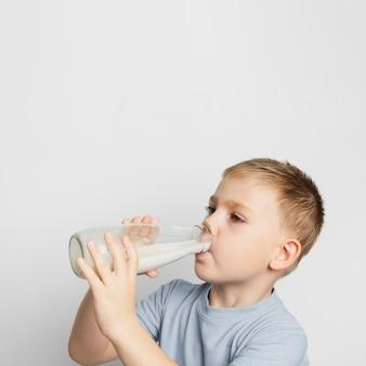 Garoto bebendo leite com garrafa