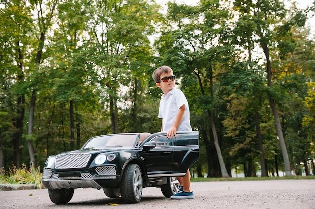 Garoto bonito andando de carro elétrico preto no parque