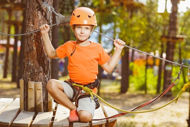 Garoto bonito aparece com o polegar para cima com equipamento de escalada em um parque de aventura