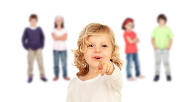 Garoto bonito, apontando com o dedo com o fundo de outras crianças