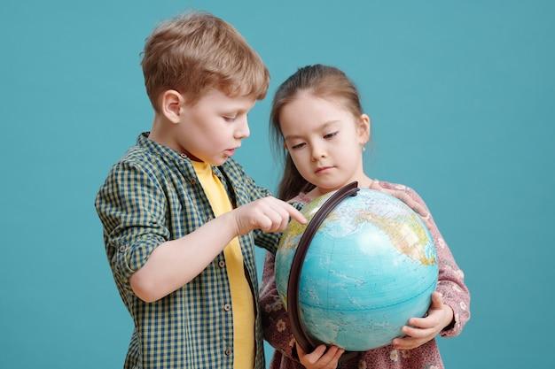 Garoto bonito apontando para o globo na mão de uma garotinha adorável