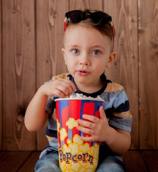 Garoto bonito bebê menino 2-3 anos de idade, óculos de cinema 3d segurando balde de pipoca, comendo fast-food em fundo de madeira. conceito de estilo de vida de infância de crianças. copie o espaço