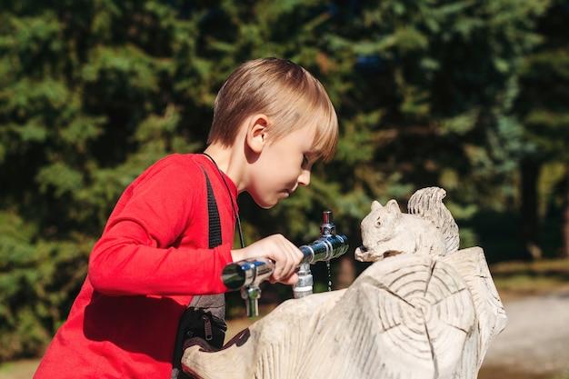 Garoto bonito bebendo água da torneira da rua.