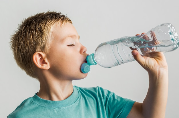 Garoto bonito beber água de uma garrafa de plástico