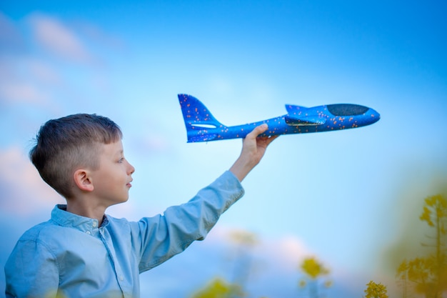 Garoto bonito brinca com um avião de brinquedo no céu azul e sonhos de viajar. mão com o avião de brinquedo azul.