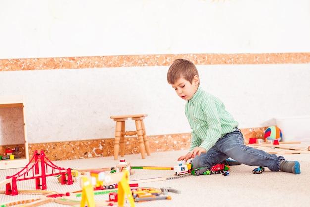 Garoto bonito brincando com a estrada de ferro de brinquedo no chão