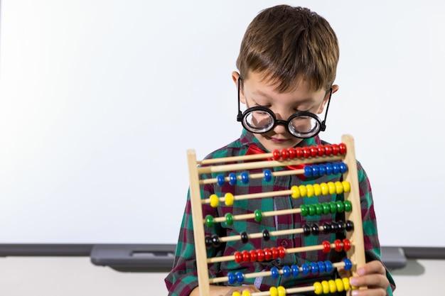 Garoto bonito brincando com ábaco na sala de aula
