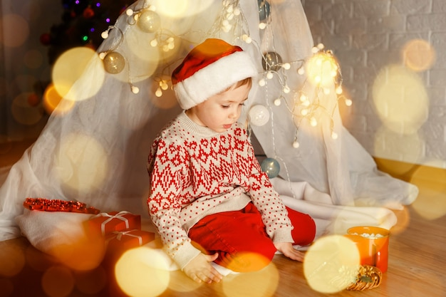 Garoto bonito brincando com presentes no chão dentro de casa no dia de natal