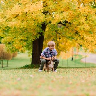 Garoto bonito brincando e andando com seu cachorro na campina