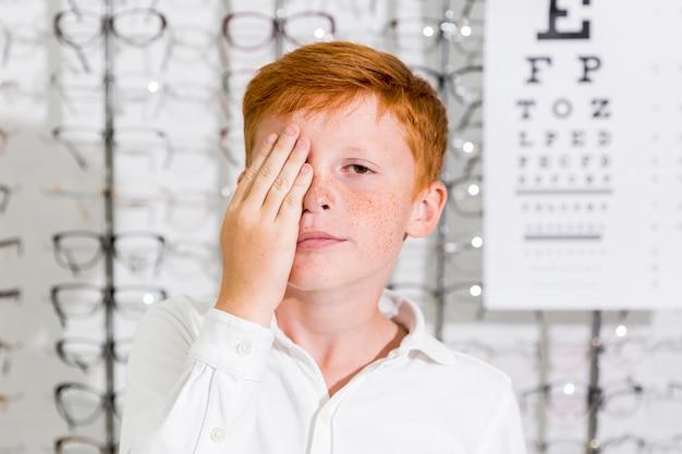 Garoto bonito cobriu o olho com a mão em pé na clínica de óptica