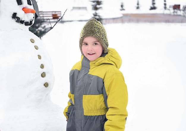 Garoto bonito com boneco de neve no parque nas férias de inverno