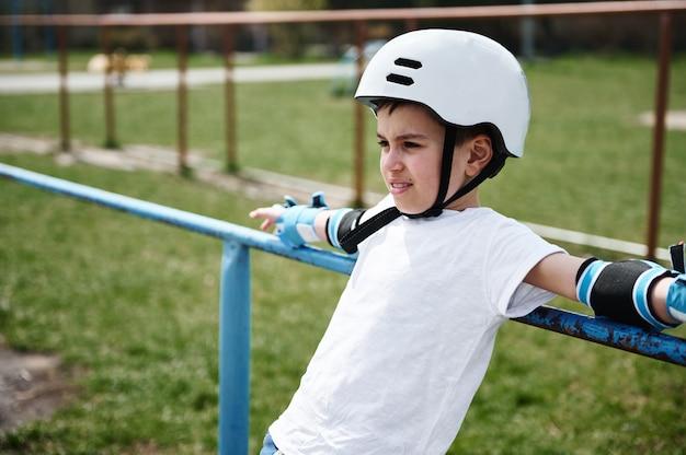 Garoto bonito com capacete de segurança e equipamento de proteção encostado na barra horizontal no parquinho ao ar livre