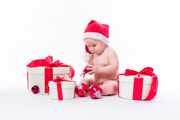 Garoto bonito com presentes de natal e chapéu de papai noel