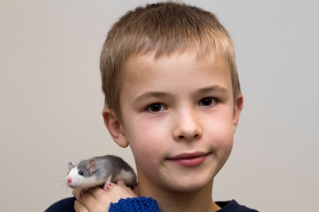 Garoto bonito com rato de estimação branco no ombro