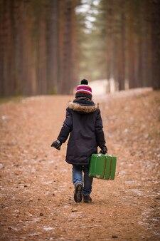 Garoto bonito com um chapéu, um pompom e uma jaqueta quente caminha pela floresta com uma mala verde