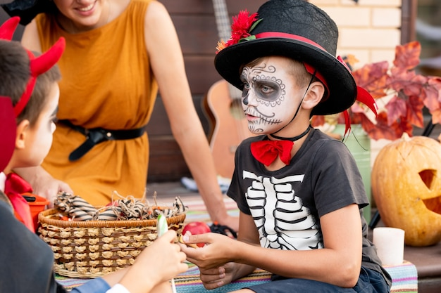 Garoto bonito com uma fantasia de halloween, olhando para o amigo, enquanto os dois se deliciavam com uma jovem sentada perto