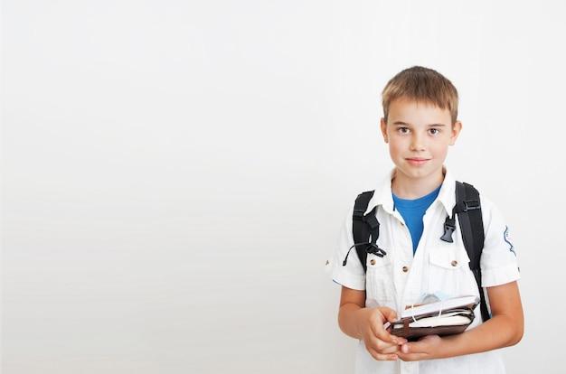 Garoto bonito com uma mochila em um fundo cinza com espaço de cópia. nas mãos de cadernos e uma máscara médica. aprendizagem, educação, conceito de escola