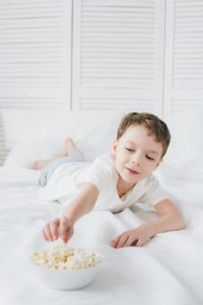 Garoto bonito comendo pipoca sentado na cama com lençóis brancos