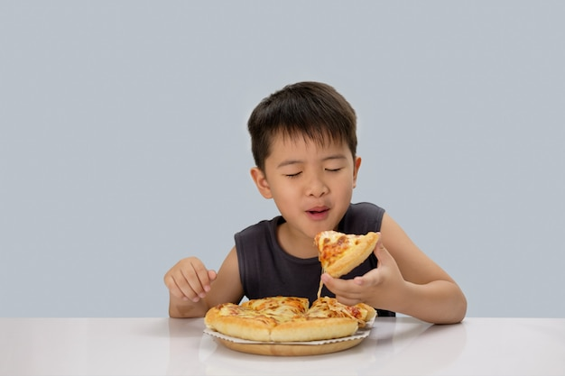 Garoto bonito comendo pizza isolado em fundo azul