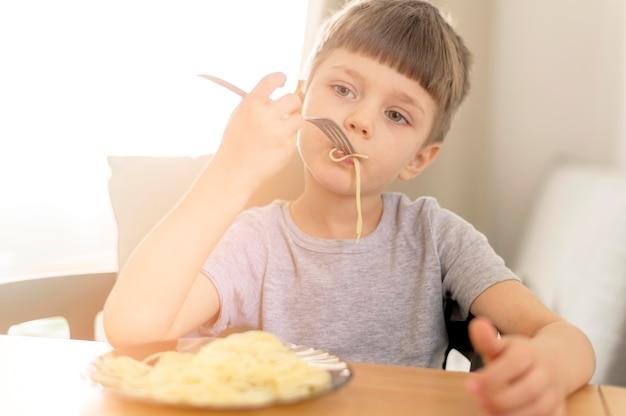 Garoto bonito comer espaguete