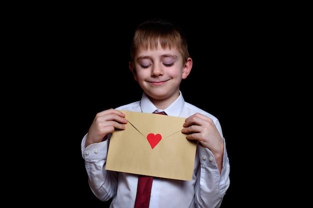 Garoto bonito de camisa e gravata segura um envelope com um coração. isolar