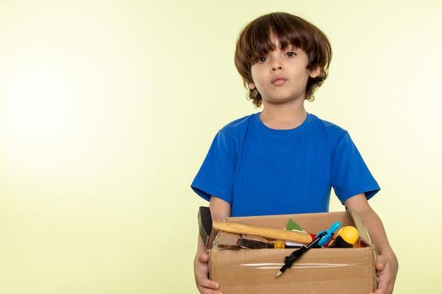 Garoto bonito de camiseta azul, segurando a caixa com ferramentas na parede branca