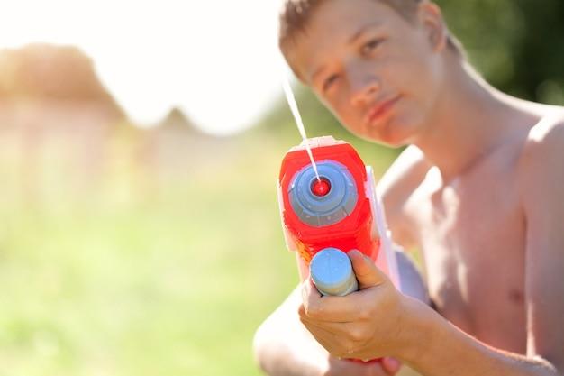 Garoto bonito de óculos brincar com pistola d'água em um dia quente e ensolarado de verão