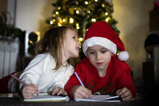 Garoto bonito de suéter vermelho e chapéu de papai noel vermelho escreve uma carta para o papai noel